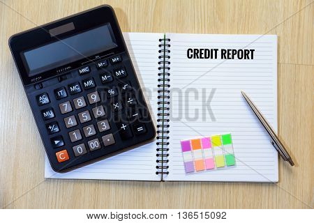 Credit report on notepad with calculator colorful bookmark and pen.