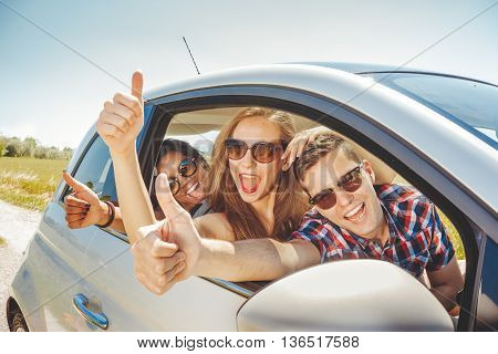 friends having fun in car - 3 young cheerful people out in a car travelling while on a summer trip