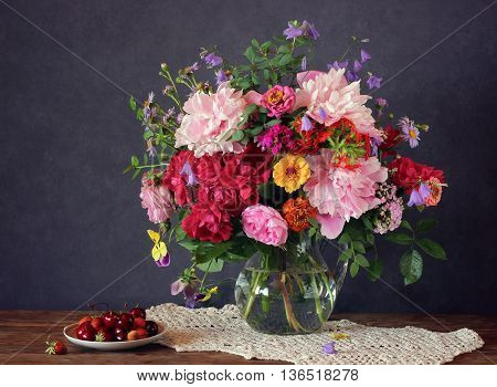 Still life with a summer bouquet of roses peonies and other flowers and cherry.