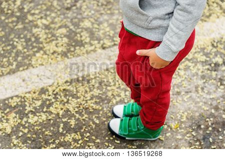 Little boy in red joggers and green shoes