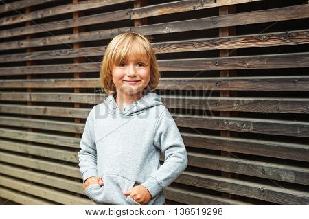 Fashion portrait of adorable toddler boy wearing grey sweatshirt, standing against wooden background