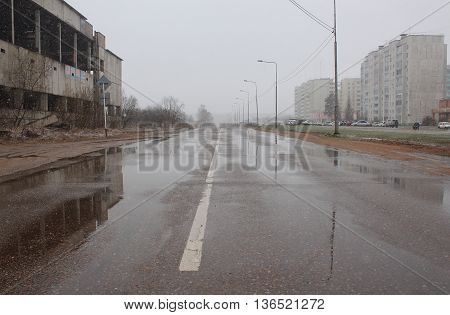 The wet road during the rain next to the abandoned unfinished home