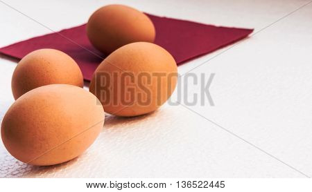 four eggs in a shell of orange color lie on a light uneven surface, the claret tissue is in the distance visible