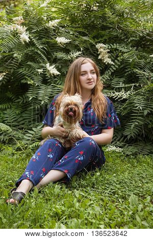 stylish big happy girl sitting on the grass in the park with a dog in her arms
