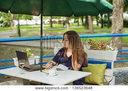 cute big size girl sitting and working on a summer ground in a cafe at a table under an umbrella and writes in a notebook near a laptop a cup and a glass of wine or water and cake.