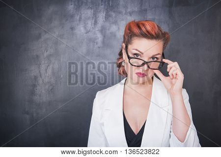 Serious Teacher In Glasses On Blackboard Background
