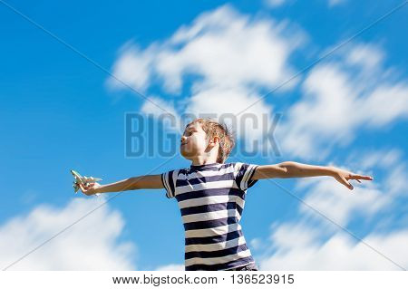 flight of the imagination. happy boy playing with a toy airplane on a background of blue sky. blurred motion due to the concept. copy space for your text