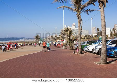Parked Vehicles And People On Beach Front