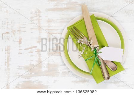 White and green plates green linen napkin vintage fork and knife tied with a green satin ribbon and small white flowers on an old wooden table; top view flat lay overhead view; with space for text