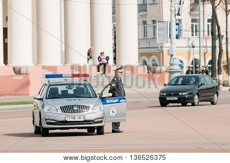 Gomel, Belarus - April 10, 2015: A policeman stands next to a patrol car in the background Dramatic theater in Gomel.