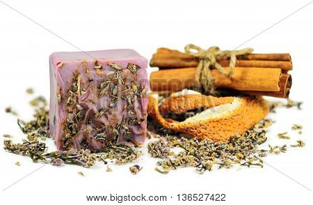 Violet scrub soap bar at cinnamon and orange peel background isolated on white