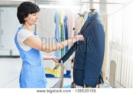 Female worker in Laundry service the process of working on universal automatic equipment for steaming, Ironing and cleaning of blazers to the dry cleaners