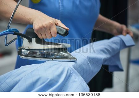 Hands smoothing the shirt with the iron