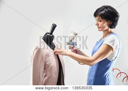 Girl Laundry worker performs painting leather jackets on a mannequin