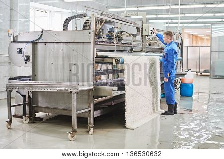Laundry worker in the process of working on automatic machine for carpet washing in dry cleaning