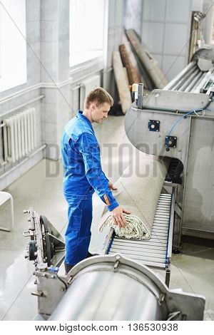 Male worker cleaning get carpet from an automatic washing machine and carry it in the clothes dryer in the Laundry room