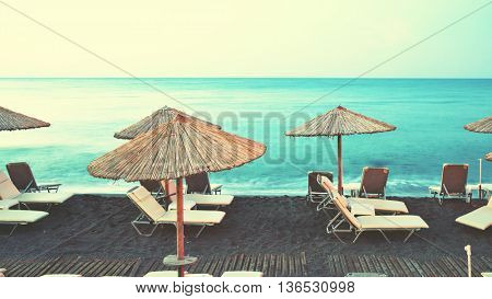 Deck chairs and umbrellas at a beach. Retro style filtered image