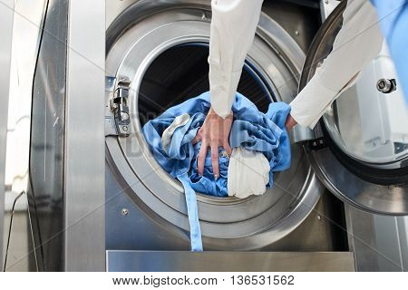 Hands to load the Laundry in the washing machine at the dry cleaners