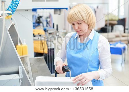 Woman worker in the Laundry process stain removal using a special dry-cleaning