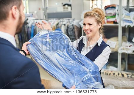 Girl worker Laundry man gives the client clean clothes at the dry cleaners