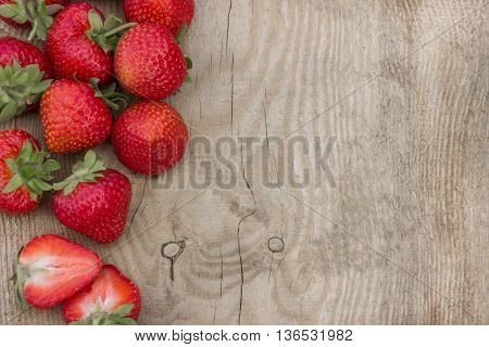 Scattered strawberries on wooden table (can be used as background, card)
