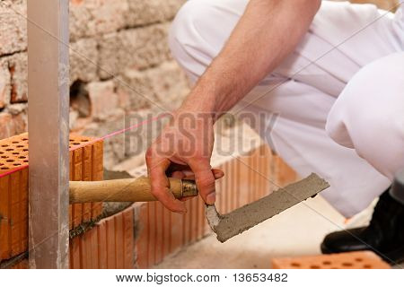 bricklayer laying bricks to make a wall, he is checking his work