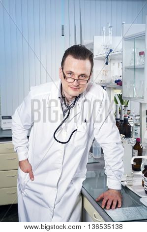 Doctor with stethoscope glasses and robe costs near a table in laboratory