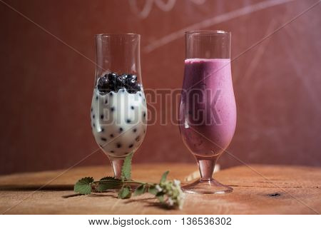 milkshake of blueberries two glasses on a wooden table a berry smoothie and the inscription Menu
