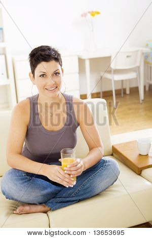 Young woman sitting on sofa at home, drinking orange juice.