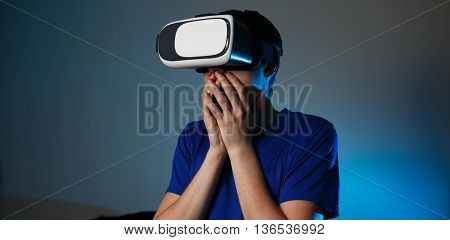 Man wearing virtual reality goggles at home. VR concept with emotions.