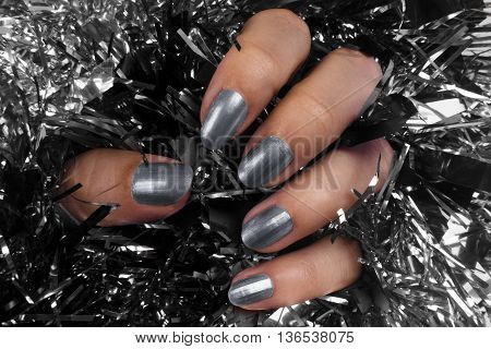Female hand with gray nails on black and silver texture background.