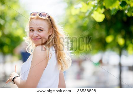 Portrait of pretty blond girl with sunglasses on head and white blouse loking back and smiling