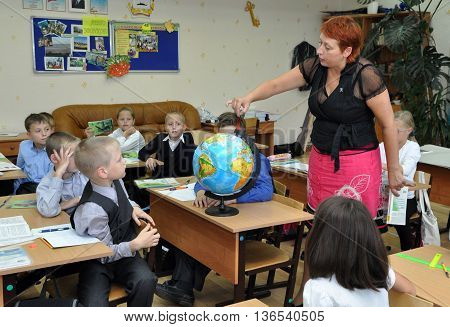 Murmansk russia - September 17 2013 Children studying geography in the classroom using the Globe