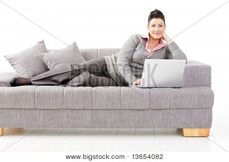 Woman lying on sofa at home working on laptop computer. Isolated on white background.?