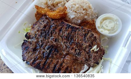 BBQ and Seafood Combo featuring New York Steak Fried Shrimp Rice cabbage and tarter sauce in a styrofoam plate.