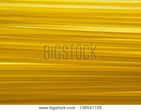 Yellow long spaghetti on black background. Thin pasta arranged in rows. Yellow italian pasta. Long spaghetti. Raw spaghetti wallpaper.