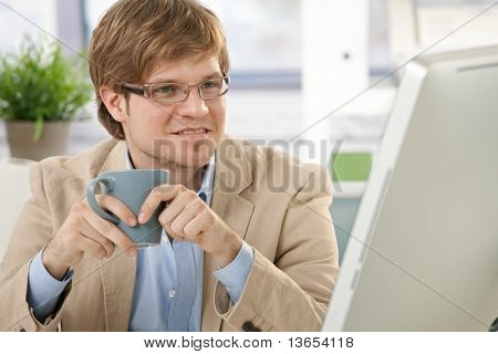 Young businessman sitting at office desk, holding coffee cup, looking at screen.?