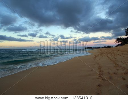 Dusk on Sunset Beach with ocean waves moving to shore and foot prints in the sand on the North Shore of Oahu. January 2016.