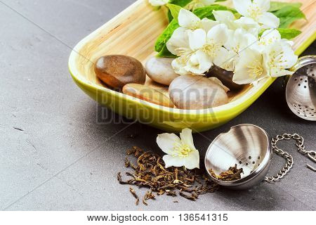 Tea infuser with dry green tea leaves and fresh jasmine flowers