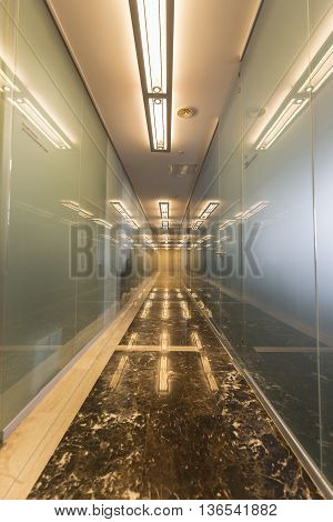 Modern office corridor with glass doors and reflections