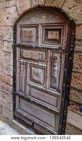 Old vintage wooden door with carved handle in Israel