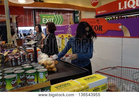 NAPERVILLE, ILLINOIS / UNITED STATES - NOVEMBER 3, 2015: Shoppers place their purchases on the conveyor belt at the check out line in the Super H Mart Korean supermarket in Naperville.