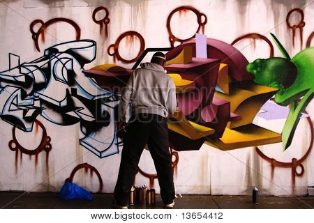 Unidentified man sprays graffiti on a wall like a vandal