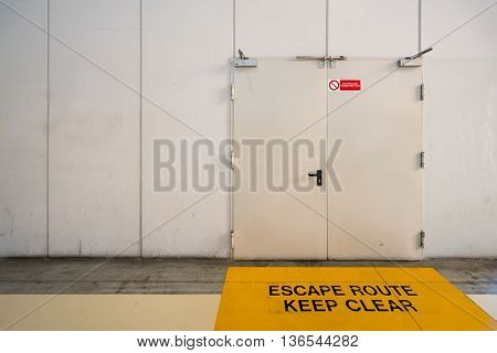 Emergency exit door with keep clear warning message on floor copy space on wall