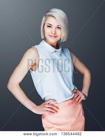 confident smiling young woman against grey studio background