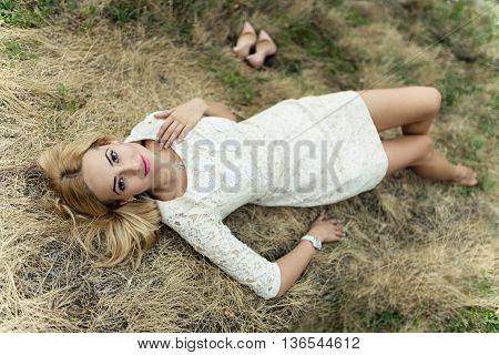 Styled portrait of beautiful sexy young woman lying in the hay