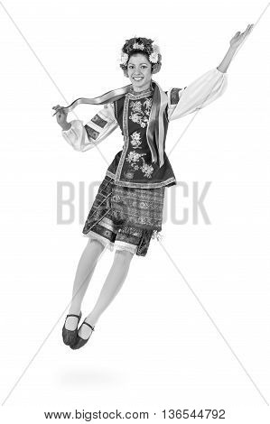 colorless full length portrait of dancing girl in polish national traditional costume jumping, isolated over white background