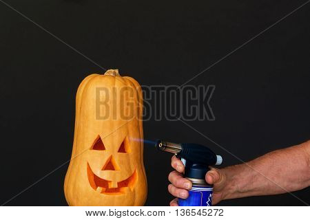 Carved smiling Scary Halloween pumpkin hand with running burner, preparation for the holiday