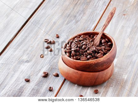 roasted coffee beans in a wooden bowl on the table, selective focus