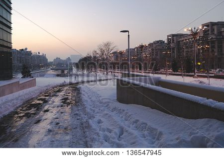 BUCHAREST, ROMANIA - January 22, 2016: View over Dambovita river and Unirii Boulevard towards the Parliament building at sunset on a winter day. BUCHAREST - January 22 2016